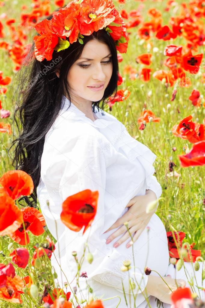 3a16b9f4c42 Pregnant woman is wearing white dress and wreath is resting on poppy field  — Photo by ...