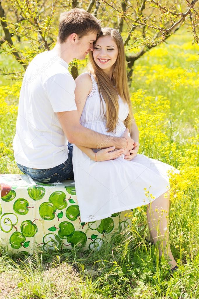 Happy couple girl with boyfriend in flowers garden