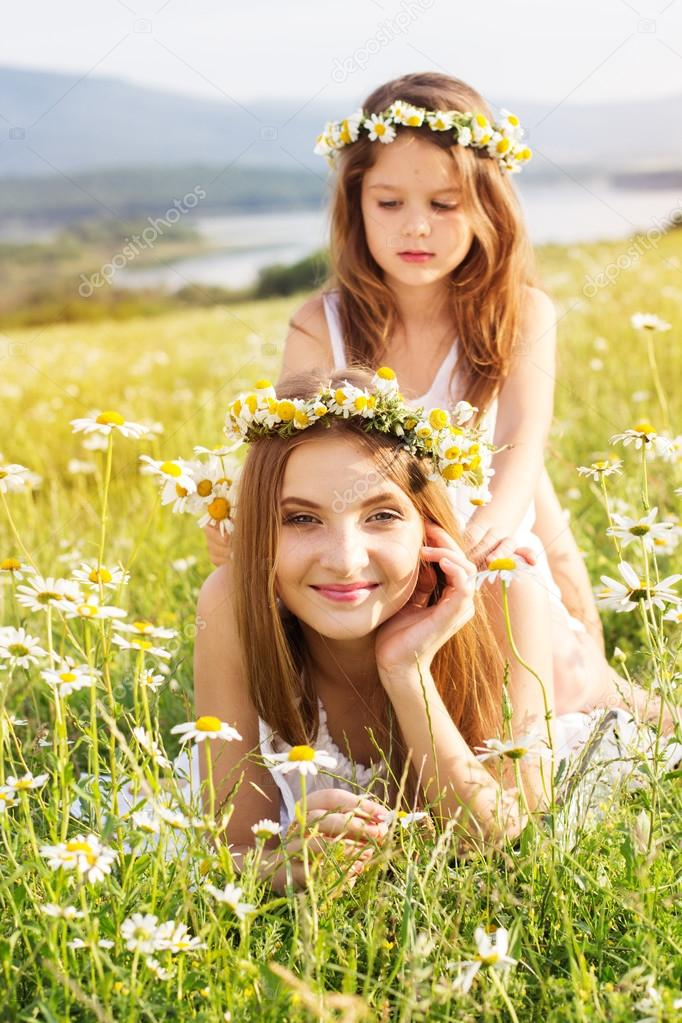 Two pretty girls at meadow with mountain view and flowers