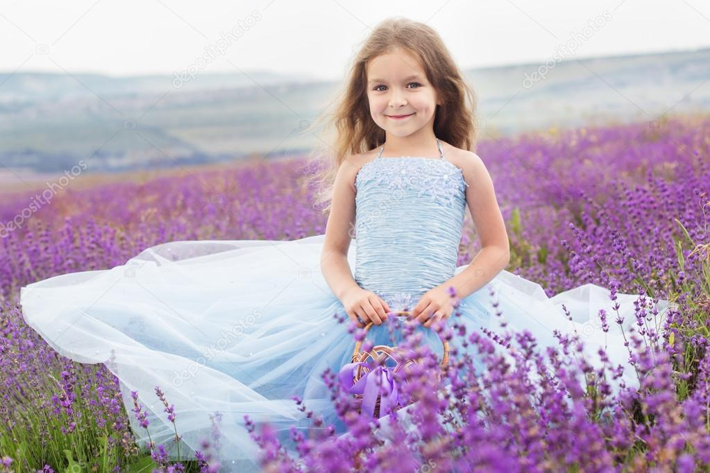 Happy little girl in lavender field with basket