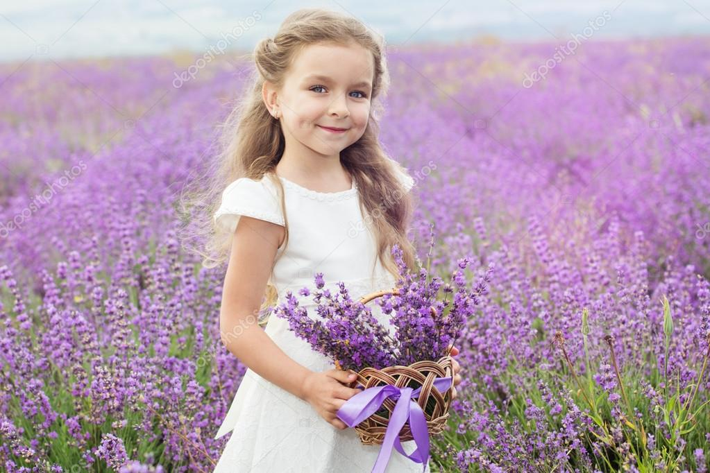 Pretty child girl in lavender field with basket of flowers