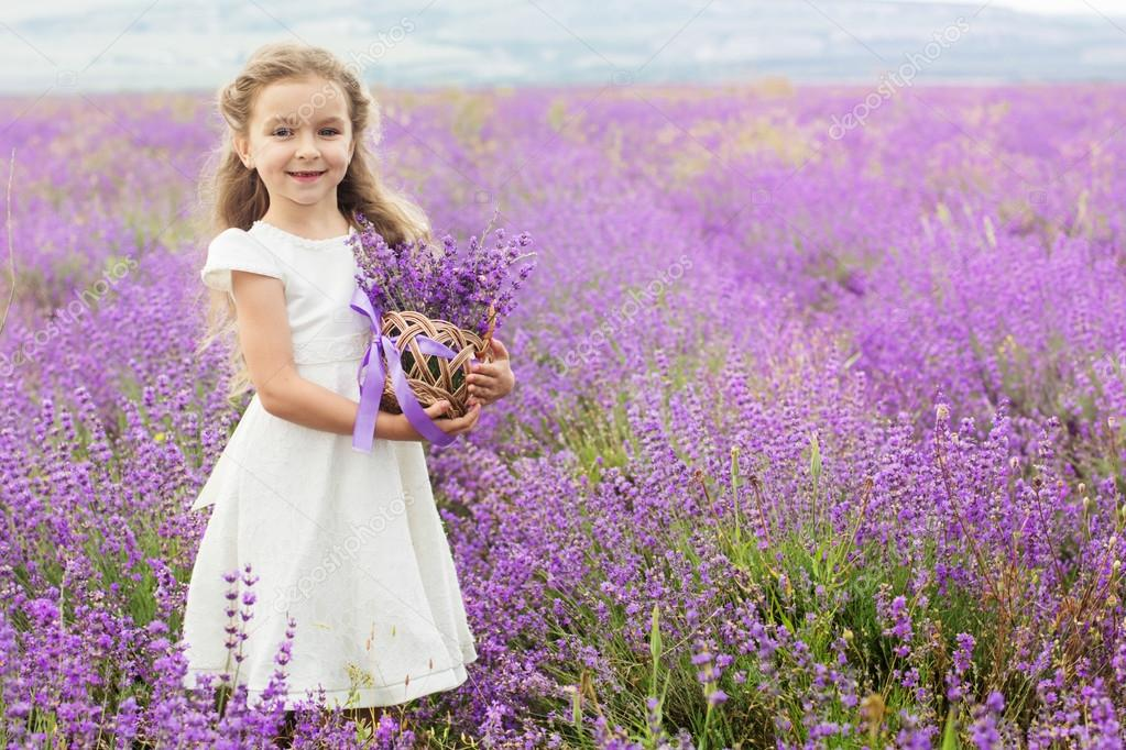 Pretty little girl in lavender field with basket of flowers