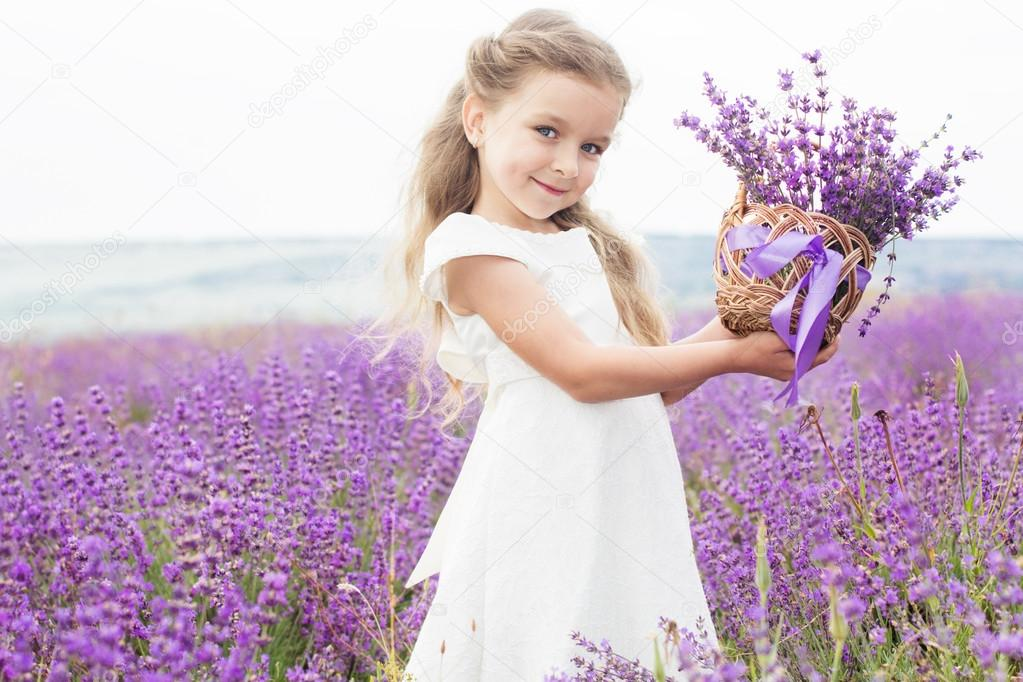 Happy little girl in lavender field with basket of flowers