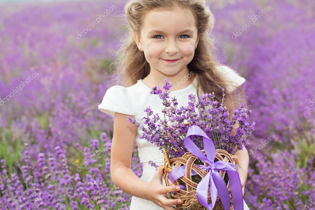 Happy little girl in lavender field with basket