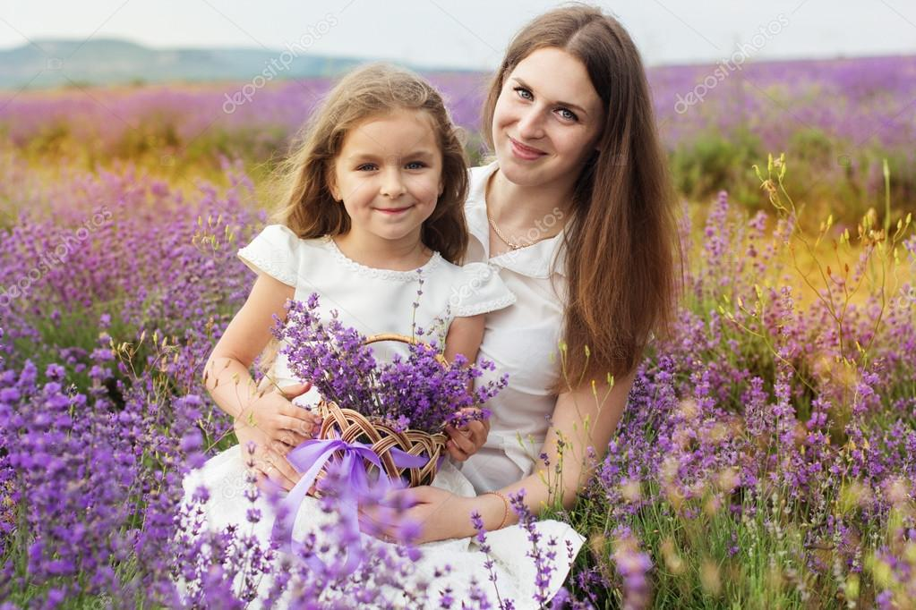 Child girl with mother in lavender field are holding basket