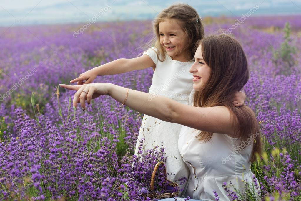 Mother with daughter in lavender field are holding basket