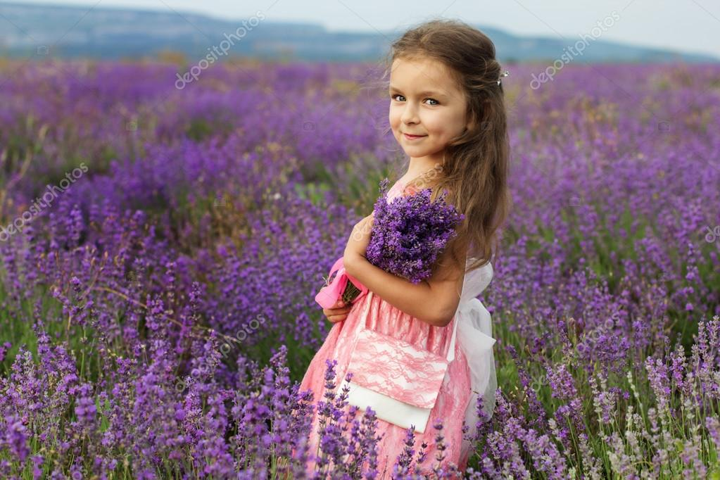 Cute little child girl in lavender field with bouquet