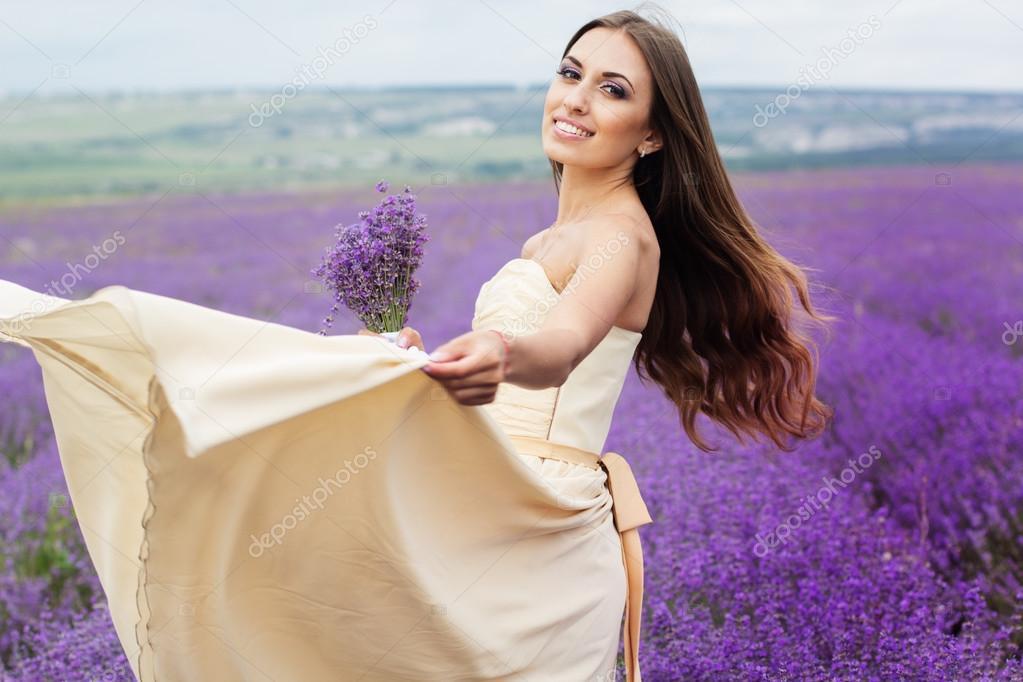 Pretty girl is wearing wedding dress at purple lavender field