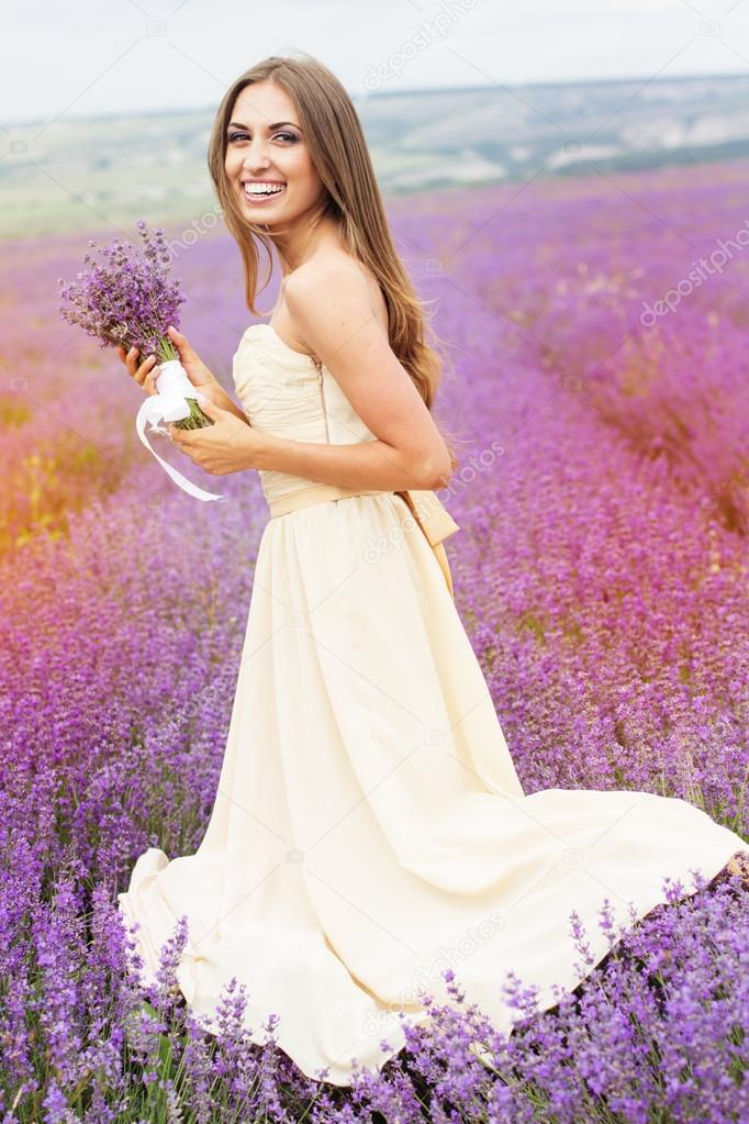 Pretty smiling girl is wearing dress at purple lavender field