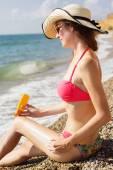 Fotografie Pretty woman applying sunscreen lotion on her legs