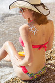 Fotografie Sunscreen lotion over tan womans back with birthmarks