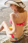 Sunscreen lotion over tan womans back with birthmarks