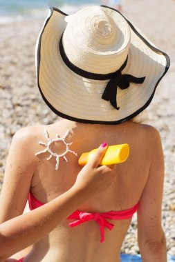 Friend applying sunscreen lotion over tan woman back