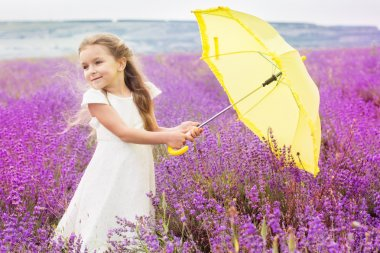 Happy little child girl in lavender field with yellow umbrella