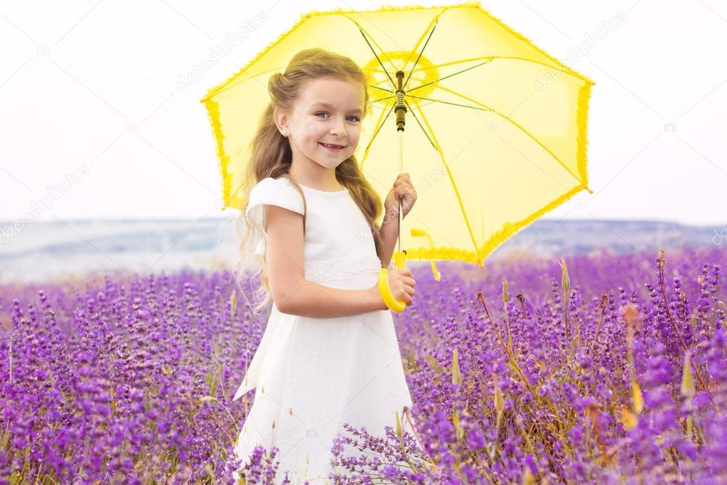 Happy cute little girl in lavender field with yellow umbrella