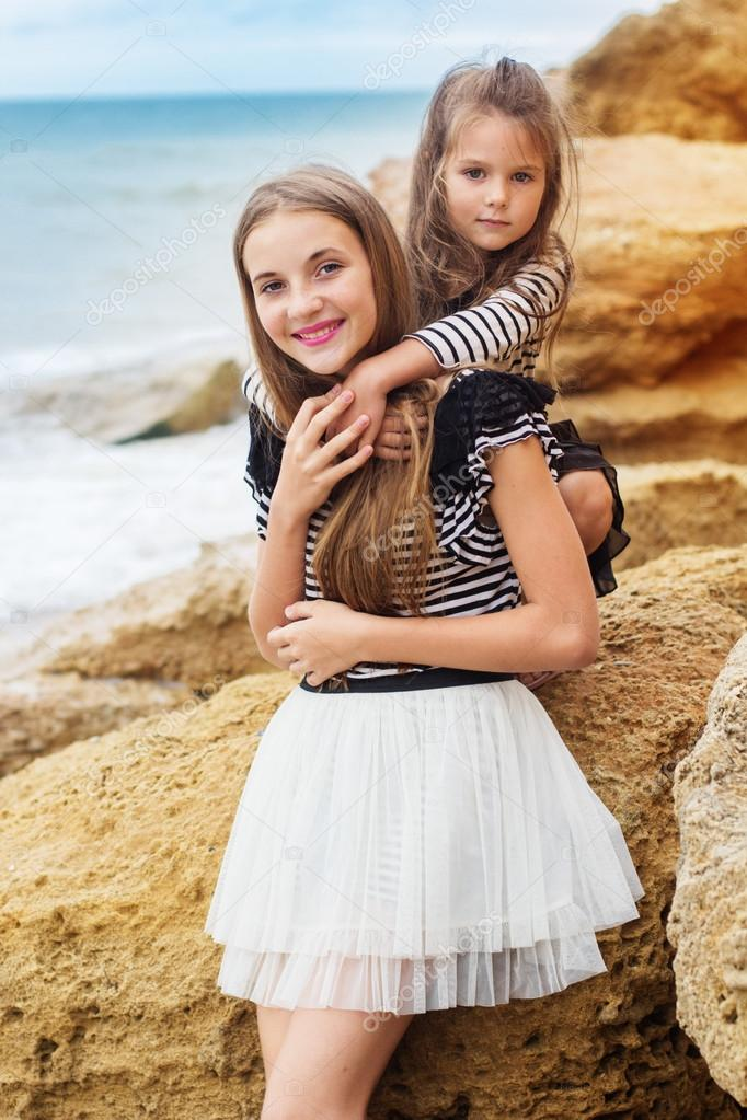 Portrait of two friends girls sitting on the beach