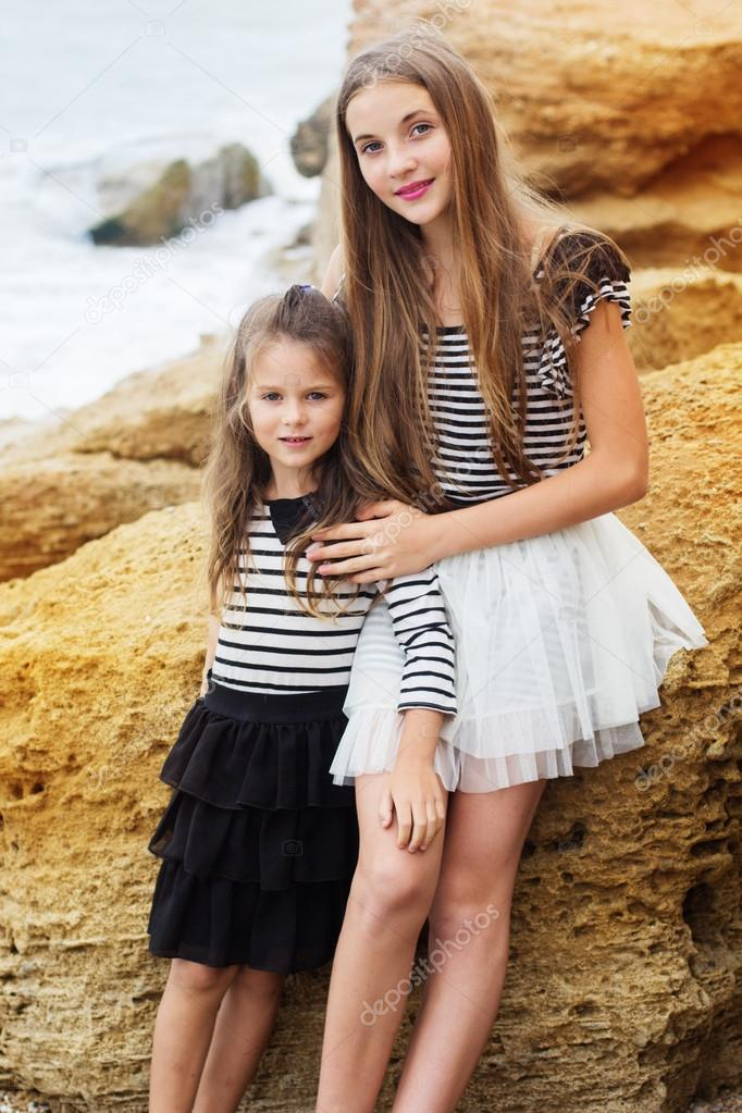 Portrait of two pretty friends girls sitting on the beach