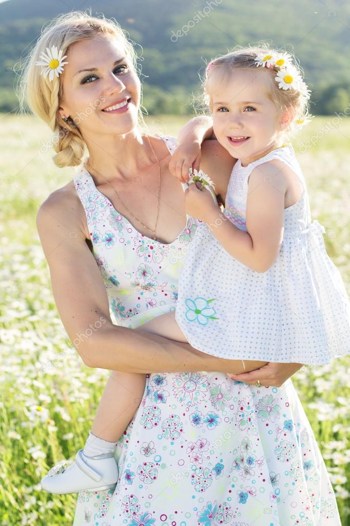 Happy family mother and daughter in field of daisy flowers