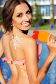 Fotografie Sunscreen lotion on girls shoulder near swimming pool