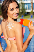 Sunscreen lotion on girls shoulder near swimming pool