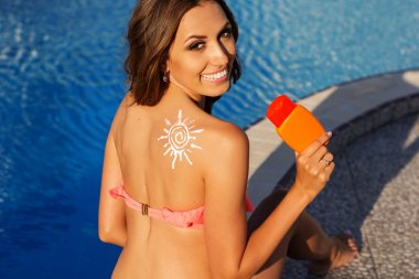 Sun shape drawing from sunscreen lotion on girls shoulder