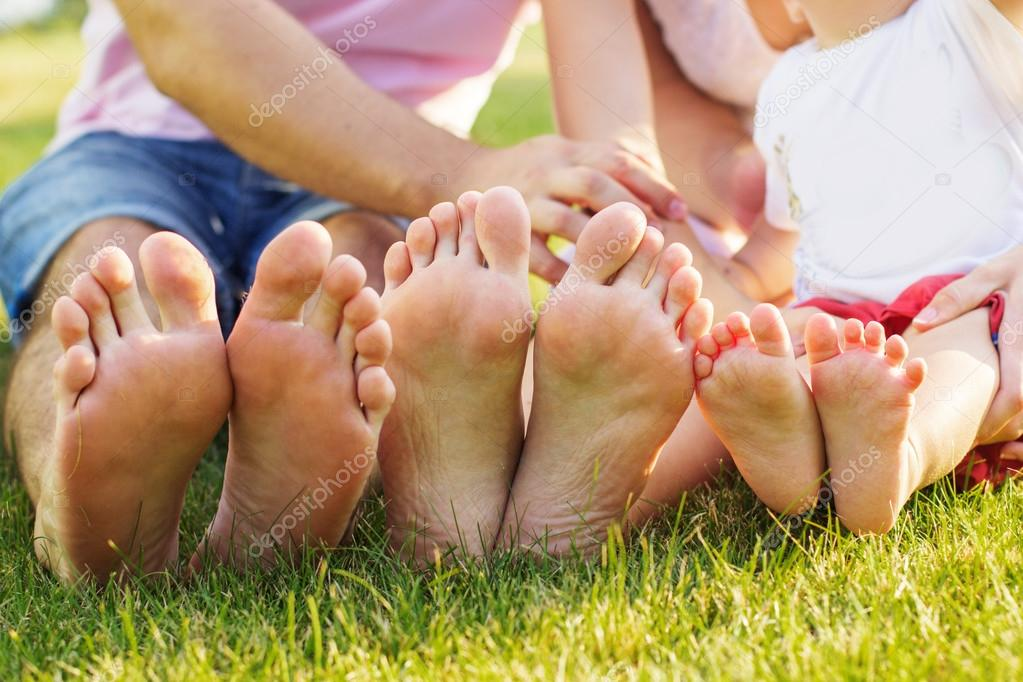 Closeup photo of feets lying in line at green grass