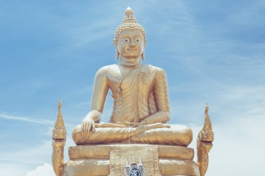 Sitting Buddha statue in Thailand over blue sky