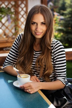 Pretty young woman drinking coffee in a cafe