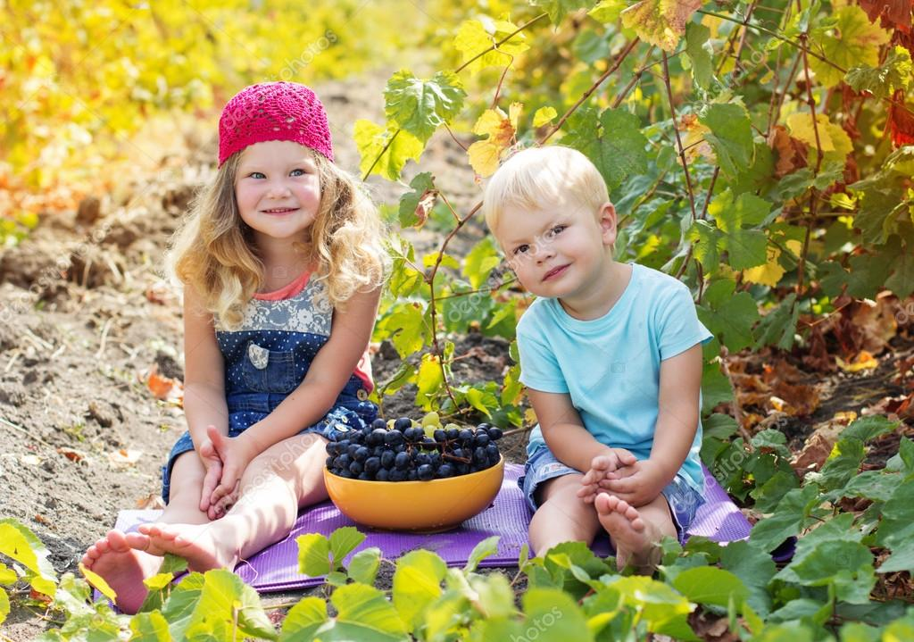 Childrens are heating grapes outdoor during autumn