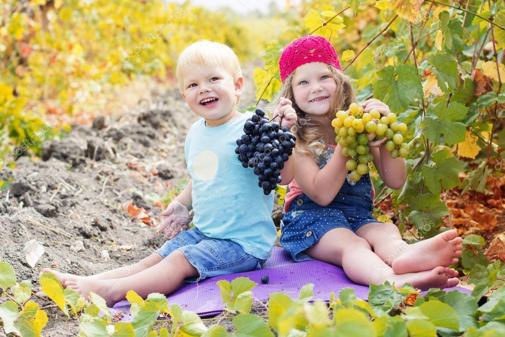 Happy childrens are holding buhch of grapes outdoor