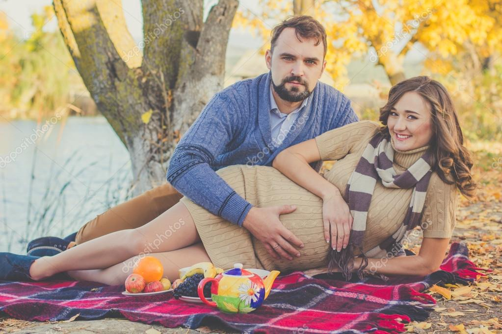 414a9ae1082 Happy future parents wife and husband are wearing warm clothes spending  time on the picnic with tea and fruits in autumn park near lake — Photo by  ...