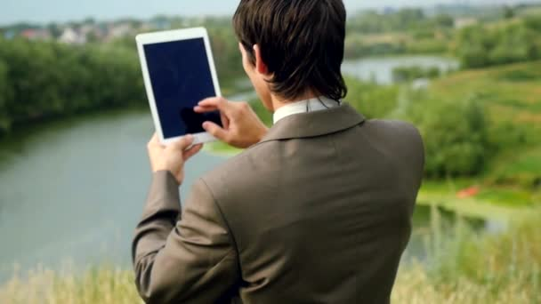 Young businessman standing on edge of rock mountain and using tablet pc. 4k. 3840x2160
