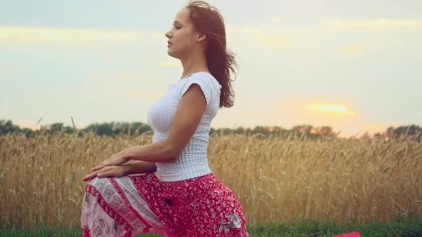 Beautiful young woman doing yoga exercise on wheat  field in slowmotion. Yoga concept. 1920x1080