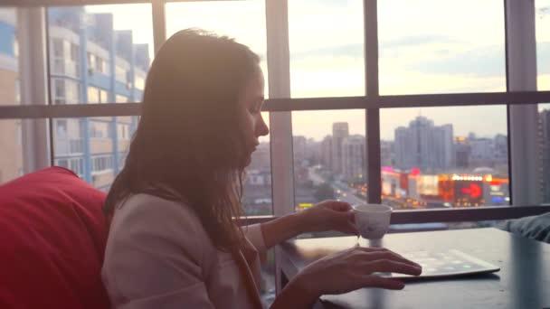 Vážné mladá podnikatelka pomocí tabletu pije čaj, posezení v restauraci s krásným výhledem z okna na rozmazané město světel a bokeh, odlesk objektivu. 4k