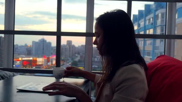 Škaredě mladá žena pomocí tabletu pije čaj, posezení v restauraci s krásným výhledem z okna na rozmazané město světel a bokeh. 4k