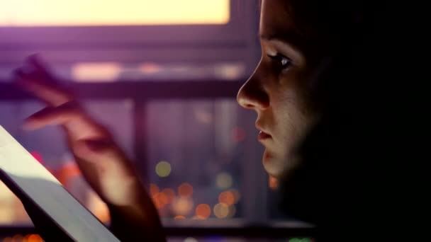 Woman using tablet with sunbeams and lens flare Business girl young adult against twilight sky window on bokeh blurred urban background. 4k