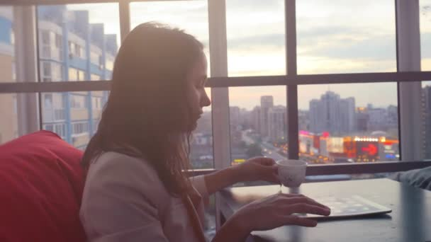 Serious young businesswoman using tablet drinks tea sitting in a restaurant with beautiful view from window on blurred city in lights and bokeh, lens flare. 1920x1080