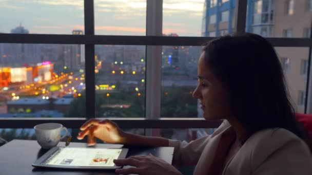 Serious young business woman using tablet drinks tea sitting in a restaurant with beautiful view from window on blurred city in lights and bokeh. 1920x1080