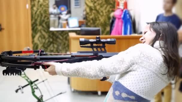 schöne junge Mädchen mit Arbalest schießt mit einer Armbrust in den Strich in Zeitlupe. 1920x1080