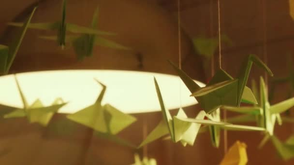 Origami Swans Hanging Under The Lights As An Ornamental Decoration