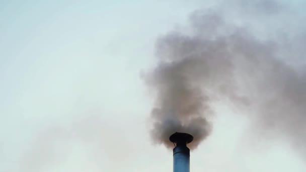 Komín kouření na střeše domu před večerní obloze v slowmotion
