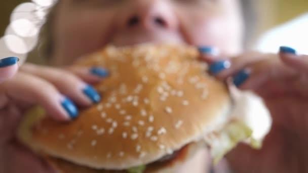 Fiatal Éhes Nő Harapás Vegán Húsgombóc Burger A Fast Food Restaurant. Egy hamburgert evő lány. Közelkép felvétel. A gyorskaja eszik. Burger női kézben.