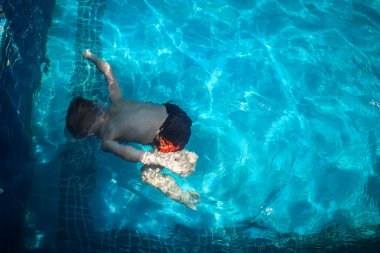 boy swims into blue swimming pool under water in resort. Koh Samui
