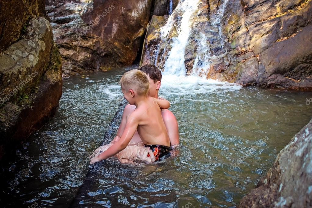 Cheerful dad and son bathe in the waterfall on Koh Samui