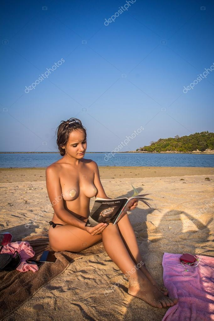 Woman wearing stickers on the breasts reading book near ocean