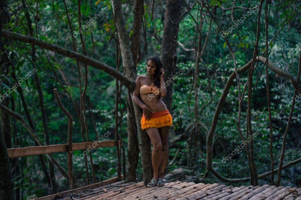 Woman posing on wooden floor background in forest