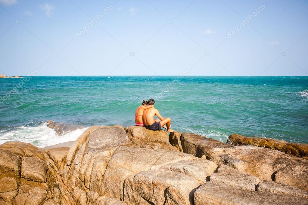 young couple sitting on the rocks near shore and hug