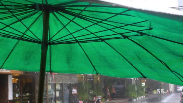 Rain drops fall from green umbrella on the street of Bangkok city. Changes focus background on blurred. HD. 1920x1080
