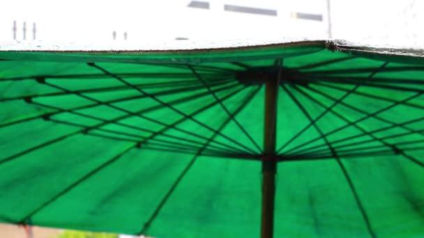 Regentropfen fallen vom grünen Regenschirm auf die Straße. Veränderungen konzentrieren sich auf verschwommene Hintergründe. hd. 1920x1080
