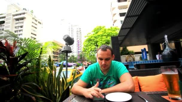 Muž sedí venkovní kavárny a pomocí smartphone. HD. 1920 x 1080
